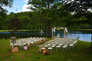 Rows of chairs set up in the grass with lake in the background ready for a wedding ceremony.