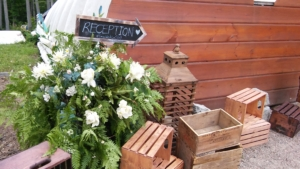 Flowers and display set up with an arrow sign that says 'Reception'.