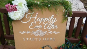 "A sign that says ""Happily Ever After Starts Here', decorated for a wedding."