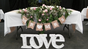 "Flower arrangement on a table with signs saying ""Love"" and ""Mr & Mrs"""