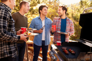 4 men with food and drink at a BBQ
