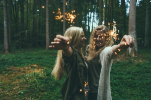 2 ladies standing outdoors at dusk with sparklers